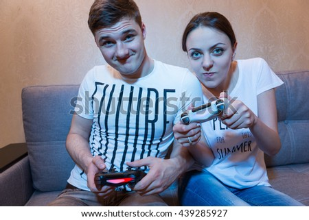 Cheerful young couple are very passionate about playing video game holding a console sitting on the sofa at home - stock photo