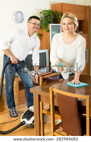Cheerful young couple cleaning in house together and smiling. Focus on the woman - stock photo
