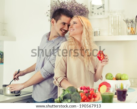 Cheerful young couple cooking together. - stock photo