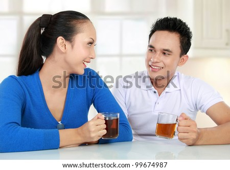 Cheerful young couple having a tea together - stock photo