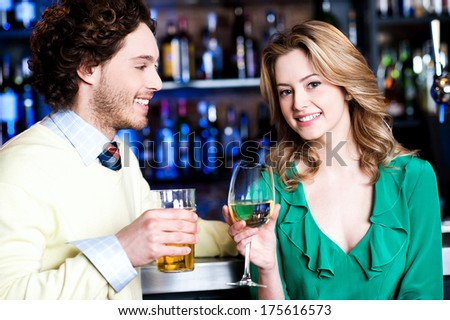 Cheerful young couple having cocktail at restaurant bar - stock photo