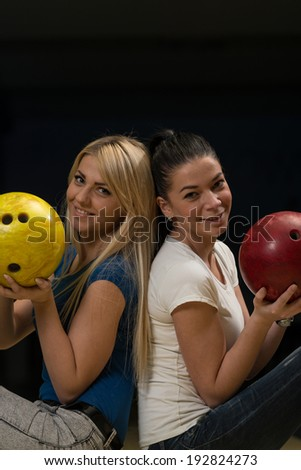 Cheerful Young Couple Holding Bowling Ball - stock photo