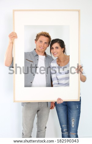 Cheerful young couple holding picture frame to look through - stock photo