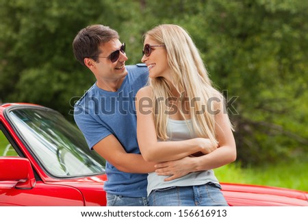 Cheerful young couple hugging and leaning against cabriolet on a sunny day - stock photo