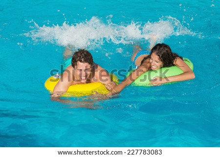 Cheerful young couple in inflatable rings at swimming pool - stock photo
