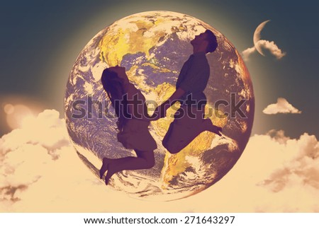 Cheerful young couple jumping against night sky - stock photo
