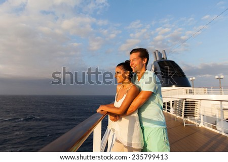 cheerful young couple looking at sunrise on cruise ship - stock photo