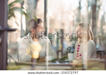 Cheerful young couple on a romantic date in a cafe - stock photo