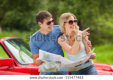 Cheerful young couple on a sunny day reading map  - stock photo