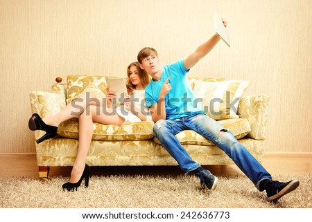 Cheerful young couple resting on a sofa and looking something on a digital tablet. They are in the cozy living room of their home.  - stock photo