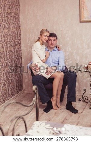 Cheerful young couple sitting indoor - stock photo