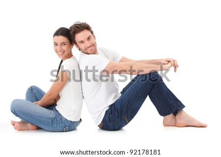 Cheerful young couple sitting with back to each other on floor, smiling happily.? - stock photo