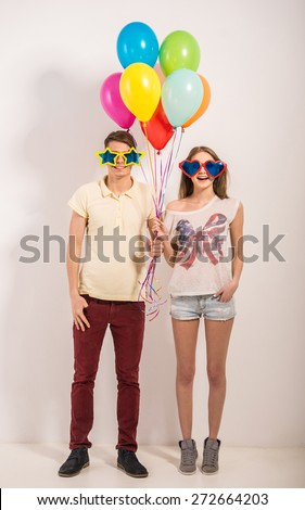 Cheerful young couple standing in funny glasses and holding colorful balloons. - stock photo
