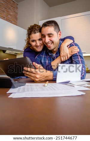 Cheerful young couple using digital tablet at kitchen home after the work. Family leisure home concept. - stock photo