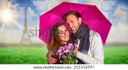 Cheerful young couple with flowers and umbrella against eiffel tower - stock photo