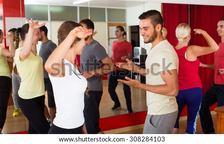 Cheerful young couples dancing active dance in studio. Selective focus