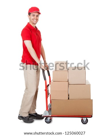 Cheerful young deliveryman in a red uniform holding trolley loaded with cardboard boxes isolated on white - stock photo