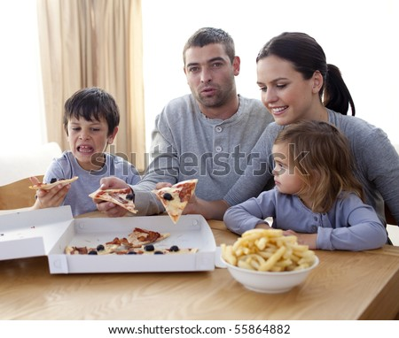 Cheerful young family eating a pizza in the living-room at home - stock photo