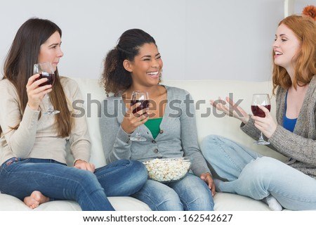 Cheerful young female friends with wine glasses and popcorn enjoying a conversation on sofa at home - stock photo