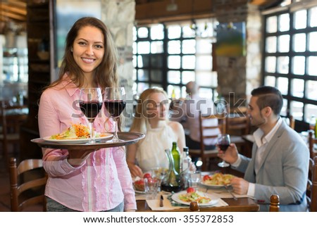 Cheerful young female waiter serving restaurant guests 