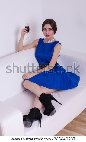 Cheerful young female with wine glasses enjoying a conversation on sofa at home - stock photo
