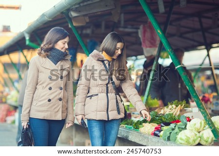 Cheerful young friends buying vegetable on the market - stock photo