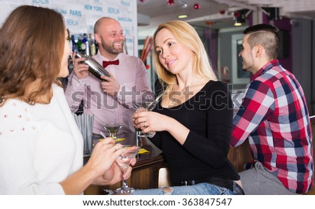 Cheerful young friends drinking and chatting with barman at bar counter - stock photo