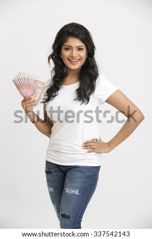 Cheerful young girl holding rupee notes in her hands on white background. - stock photo