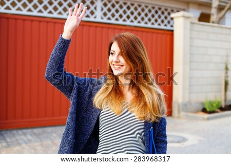 Cheerful young girl stands in the street near the red gate and waving to friends - stock photo