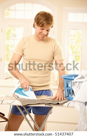 Cheerful young guy ironing clothes in bright living room. - stock photo