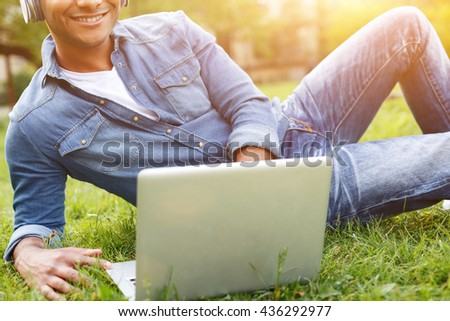 Cheerful young guy is resting in park - stock photo
