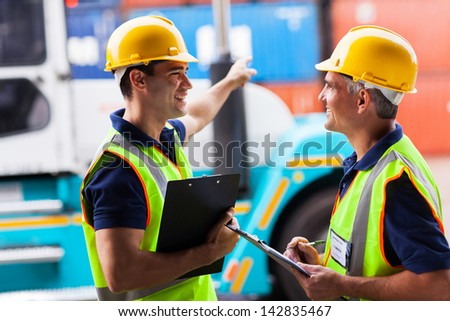 cheerful young harbor worker pointing the forklift while talking to his colleague - stock photo