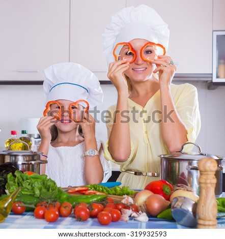 Cheerful young housewife and her daughter with veggies at kitchen table - stock photo
