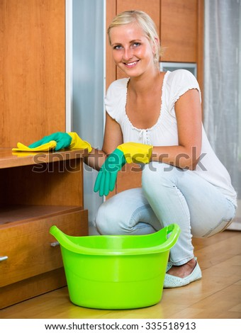 Cheerful young housewife in rubber gloves dusting furniture in living room and smiling - stock photo