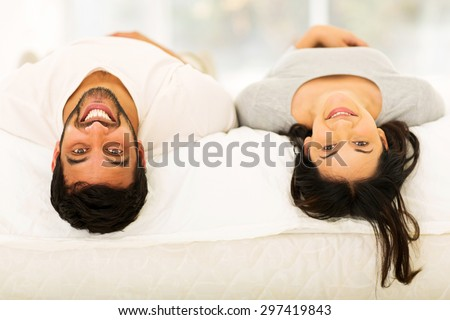 cheerful young indian couple lying on bed looking at the camera - stock photo