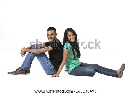 Cheerful young Indian couple sitting with back to each other on floor. Isolated on white background. - stock photo