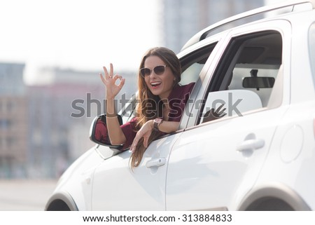 Cheerful young lady sitting in her car and showing okay sign. Businesswoman in sunglasses enjoing driving at high speed. - stock photo