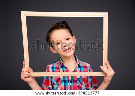 Cheerful young little boy holding wooden frame - stock photo