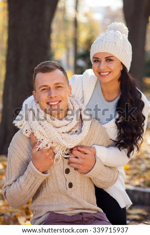 Cheerful young loving couple is dating in the autumn park. They are looking at camera and smiling. The man is sitting on bench. The woman is standing and embracing him with love - stock photo