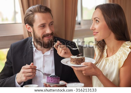 Cheerful young loving couple is eating tasty cakes in restaurant. They are sitting and drinking coffee. The pair is smiling with pleasure - stock photo