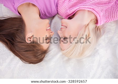 Cheerful young loving lesbian couple is lying and relaxing on bed. The women are looking at each other with love and smiling - stock photo