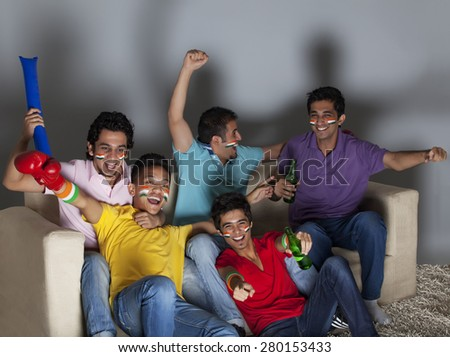 Cheerful young male friends enjoying a boxing match together at home - stock photo