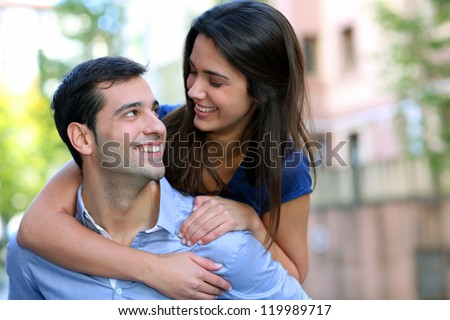 Cheerful young man carrying girlfriend on his back - stock photo