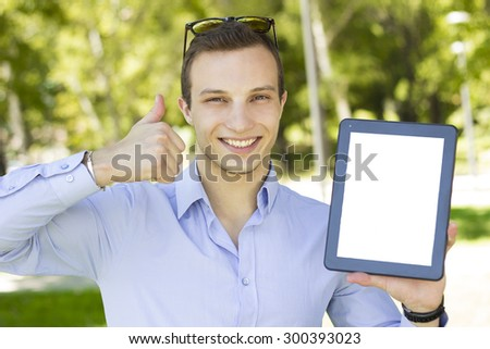 Cheerful young man holding a digital tablet in park. - stock photo