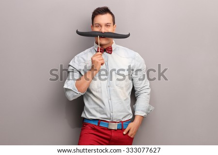 Cheerful young man holding a huge fake moustache below his nose and looking at the camera - stock photo