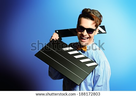 Cheerful young man holding clapper board. Cinema industry. Different occupations. - stock photo