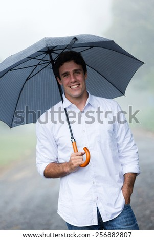 cheerful young man holding umbrella outdoors in the rain - stock photo