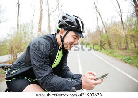 Cheerful young man in protective helmet with bicycle using mobile phone - stock photo