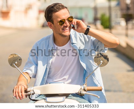 Cheerful young man in sunglasses is sitting on scooter and talking by phone. - stock photo