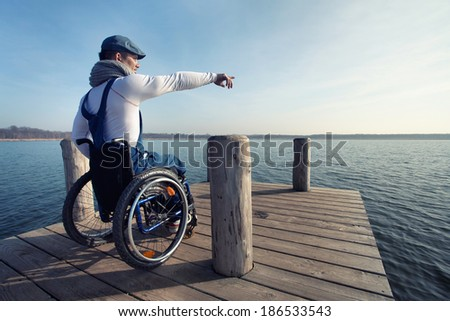 cheerful young man in wheelchair enjoying the spring on the lake - stock photo